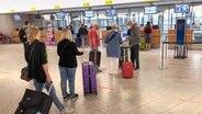 Passagiere tragen eine Mund-Nasen Maske und stehen mit ihrem Gepäck am Check-In im Flughafen Hannover.