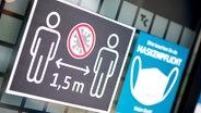 Ein Schild weist auf die bestehende Maskenpflicht und das Abstandsgebot hin. © dpa-Bildfunk Foto: Hauke-Christian Dittrich/dpa