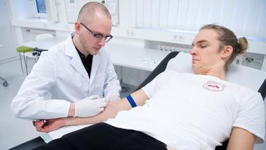 Ein Medizinstudent nimmt zur Übung einem Mitstudenten Blut ab. | dpa-Bildfunk