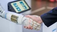 Un employé de Festo serre la main d'un robot à commande pneumatique avant le début d'une conférence de presse à la foire de Hanovre. © dpa - Photo Bildfunk: Ole Spata