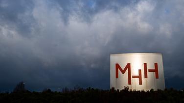 Vor dunklem, wolkenverhangenem Himmel ist ein großer Aufsteller mit dem Logo der Medizinischen Hochschule Hannover zu sehen.   dpa Bildfunk