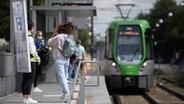 An einer Haltestelle der Hannoverschen Verkehrsbetriebe Üstra stehen mehrere Personen und tragen Mund-Nasen-Schutz. © dpa - Bildfunk Foto: Swen Pförtner