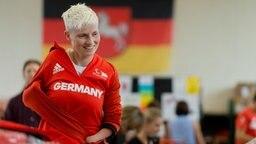 Die Tischtennisspielerin Stephanie Grebe (Borussia Düsseldorf)probiert eine Jacke an.
