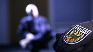 Ein Wappen der Polizei auf einem Ärmel der Uniform, im Hintergrund eine nicht erkennbare Person. © NDR Fotograf: Angelika Henkel/Stefan Schölermann