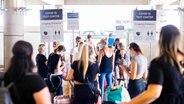 Reiserückkehrer warten in einer Schlange am Flughafen Hannover auf ihren Corona-Test. © picture-alliance