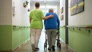 """Eine Pflegefachkraft geht mit einer Bewohnerin durch das Seniorenheim """"Mein Zuhause Nienburg"""". © picture alliance/dpa Foto: Sina Schuldt"""