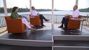 Stephan Weil sitzt in einem roten Sessel und spricht mit Martina Thorausch und Dirk Banse vom NDR. © NDR