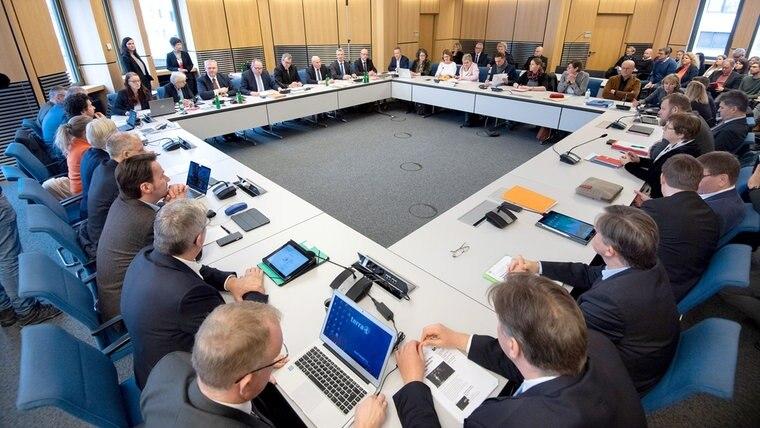 Zahlreiche Politikerinnen und Politiker sitzen in einem großen Viereck im Innenausschuss im Landtag. © dpa - Bildfunk Foto: Julian Stratenschulte