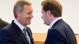 Ex-Bundespräsident Christian Wulff und der Mitangeklagte David Groenewold begrüßen sich im Landgericht Hannover. © dpa-Bildfunk Foto: Julian Stratenschulte