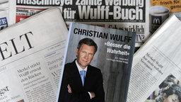 """Christian Wulffs Buch """"Besser die Wahrheit"""" liegt auf verschiedenen Zeitungen, die die Wulff-Affäre thematisieren. © dpa-Bildfunk Foto: Holger Hollemann"""