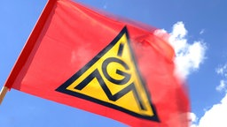 Eine Fahne der Gewerkschaft IG-Metall weht vor blauem Himmel. © dpa-Bildfunk Fotograf: Daniel Bockwoldt/dpa