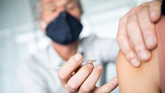 Ein Arzt impft eine Patientin gegen Grippe. © picture alliance Foto: Zacharie Scheurer