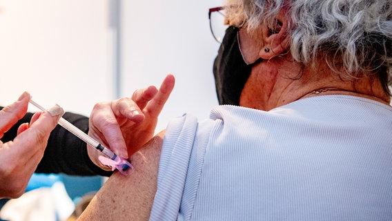 Une femme âgée est vaccinée avec une seringue. Photo alliance Photo : Robin Utrecht