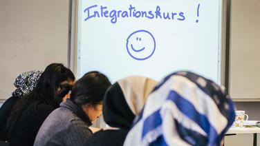 Frauen mit und ohne Kopftuch sitzen in einem Klassenraum. Auf einer Tafel steht Integrationskurs. | NDR