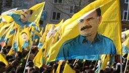 Kurdische Demonstranten tragen in Hannover Fahnen mit dem Bild von PKK-Chef Öcalan © dpa