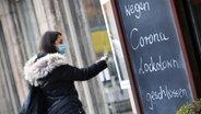 """Eine Frau steht vor einem Laden, vor dem eine Tafel steht mit der Aufschrift: """"Wegen Corona Lockdown geschlossen."""" © picture alliance Foto: SvenSimon"""