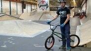 Ein Mann steht mit einem BMX-Rad in einer Halle. In der Halle sind zahlreiche Rampen aufgebaut. © NDR Foto: Alex Lofink