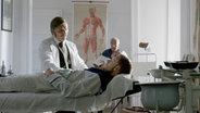 Ein Arzt behandelt einen Mann, der auf einer Liege liegt. © NDR/ Martin Christ Fotograf: Martin Christ