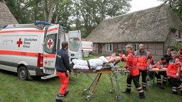 Sanitäter bringen eine verletzte Person auf einer Trage zu einem Rettungswagen. ©  dpa-Bildfunk Foto: Christian Butt