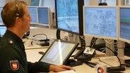 Ein Polizeibeamter schaut auf einen Computerbildschirm in der Leitstelle in Lüneburg. © NDR Foto: Dirk Drazewski