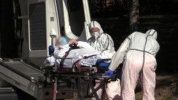 Zwei Männer in Schutzanzügen tragen einen Mann auf einer Liege in einen Krankenwagen.