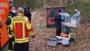 Seevetal: Polizisten untersuchen in einem Waldstück die in einem Erddepot sichergestellten Gegenstände. © Feuerwehr Seevetal Foto: Feuerwehr Seevetal