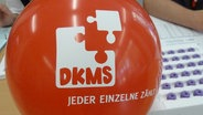 Ein roter Luftballon der DKMS liegt auf einem Schreibtisch. © NDR.de Foto: Lars Gröning
