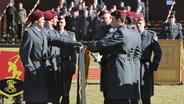 Mit der Hand auf der Bundesflagge legen Rekruten in der Panzertruppenschule in Munster das letzte Gelöbnis von Wehrpflichtigen ab. © dpa - Bildfunk Foto: Holger Hollemann