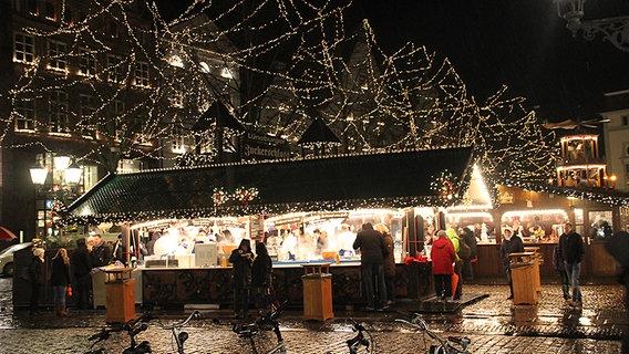 Viele Besucher stehen an den Ständen des aufwändig beleuchteten Weihnachstmarktes in der Lüneburger Altstadt. © NDR Foto: Lars Gröning