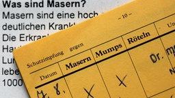 Ein Impfpass liegt auf einem Infoblatt über Masern. © dpa Foto: Achim Scheidemann