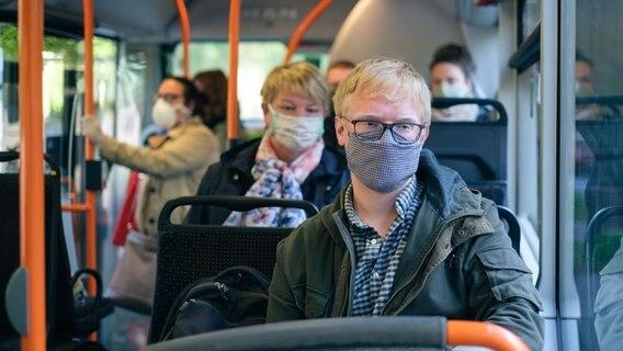Fahrgäste sitzen mit Mund-Nasen-Schutz in einem Bus. © picture alliance/Ole Spata/dpa Foto: Ole Spata