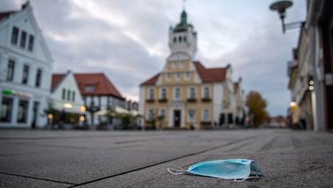Eine Mund-Nasen-Schutz liegt auf dem Boden vor dem Rathaus.   dpa - Bildfunk