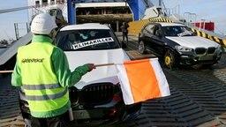 Greenpeace-Aktivisten blockieren am Autoterminal in Bremerhaven das Entladen von SUV-Fahrzeugen. © dpa - Bildfunk Foto: Bodo Marks