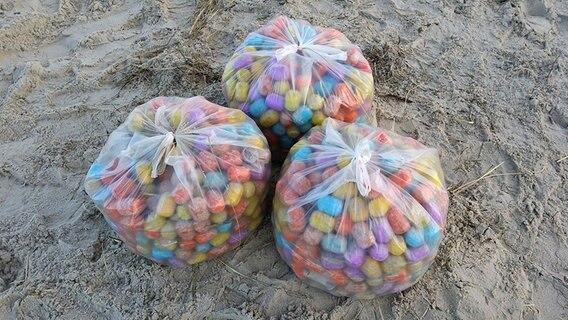 Drei Säcke voller bunter Eier stehen am Strand von Langeoog.  Foto: Thomas Pree