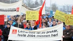 Eine Demonstration zum Thema Leiharbeit, im Vordergrund halten Menschen ein Transparent hoch. © dpa Foto: Ingo Wagner