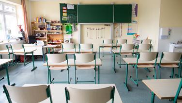In einem leeren Klassenraum einer Grundschule sind die Stühle hochgestellt.   dpa - Bildfunk