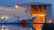 """Das Kreuzfahrtschiff """"Norwegian Breakaway"""" steht vor dem geöffneten Tor der Schiffbauhalle 6 der Meyer Werft. © dpa Foto: Ingo Wagner"""