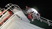 """Zwei Seenotretter der DGzRS sind mit dem Seenotkreuzer """"Anneliese Kramer"""" unterwegs. © DGzRS"""