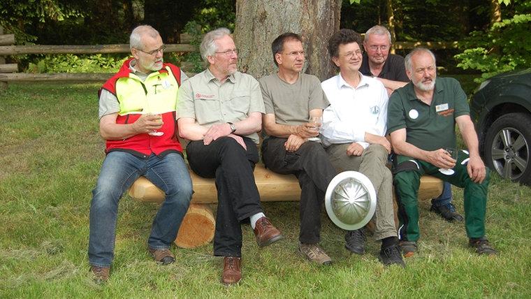 """Einige Mitglieder des Verein """"Gattersäge Upjever e.V."""" sitzen auf einer selbstgemachten Holzbank. © NDR Fotograf: Carsten Valk"""