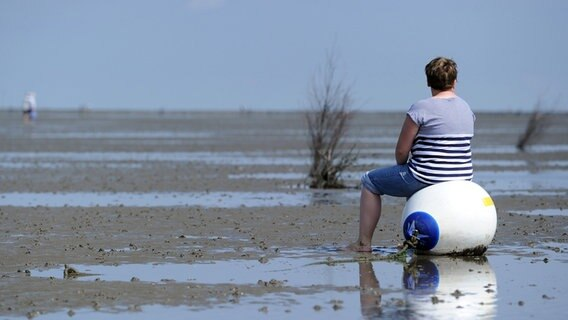 A vacationer sits on a buoy in the mudflats of the North Sea on the coast of Cuxhaven.  © dpa-Bildfunk Photo: Caroline Seidel