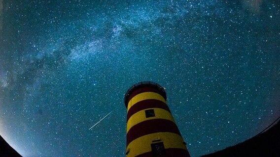 Eine Sternschnuppe leuchtet über dem Pilsumer Leuchtturm am Nachthimmel. © picture alliance / dpa Foto: Matthias Balk