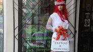 """Vor dem Tattoo-Studio """"La Donna"""" steht eine Schaufensterpuppe mit roter Perücke. © NDR Fotograf: Oliver Gressieker"""