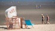 Menschen gehen an einem Strand spazieren. © dpa Foto: Sina Schuldt