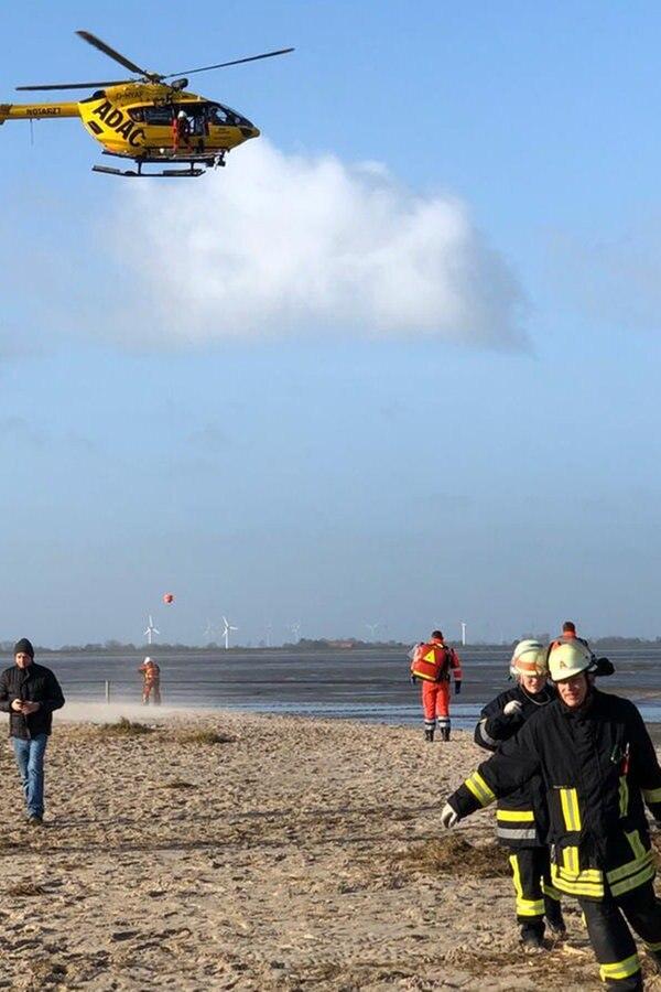 Hubschrauber zieht Wurmsammler aus dem Watt