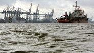 Ein Baggerschiff fährt auf der Weser vor dem Containerterminal in Bremerhaven. © dpa Bildfunk Fotograf: Ingo Wagner