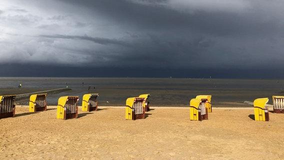 Dunkle Wolken ziehen über gelbe Strandkörbe, die am Strand stehen. © NDR Foto: Bernd Schön
