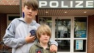 Willi und sein kleiner Bruder Moritz stehen vor der Polizeistation mit Polizeiabzeichen in der Hand. © picture alliance/--/Privat/dpa Foto: Privat