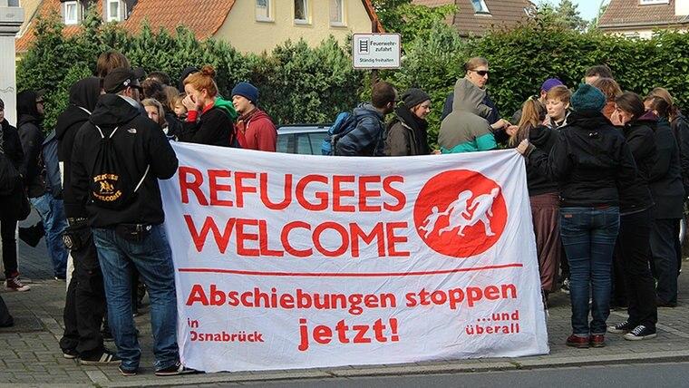 """Eine Menschengruppe steht auf einer Straße und hält ein Transparant mit der Aufschrift """"Refugees Welcome"""". © NDR Fotograf: Jörg Holzapfel"""