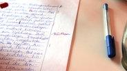 Ein Zettel mit einem korrigierten Zitat und ein Stift auf einem Tisch. © NDR Fotograf: Britta Nareyka