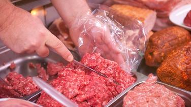Ein Mitarbeiter eines Fleischerei-Fachgeschäfts portioniert frisches Thüringer Mett. © dpa-Bildfunk Fotograf: Hauke-Christian Dittrich